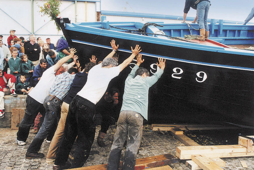 Remise à l'eau de la Bergère de Domrémy après la restauration en 2000 : en juillet 2002, au 3ème bassin du port de commerce de Brest, les charpentiers qui ont participé à la restauration poussent le bateau pour le mettre à l'eau.